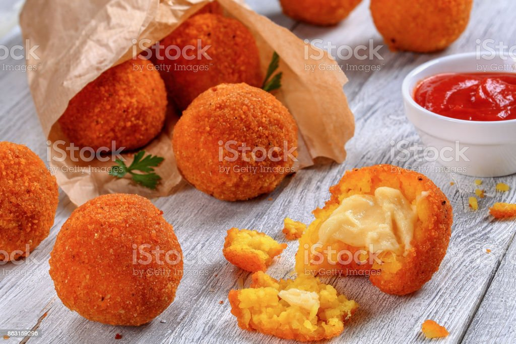 rice balls stuffed with cheese in paper cornet stock photo