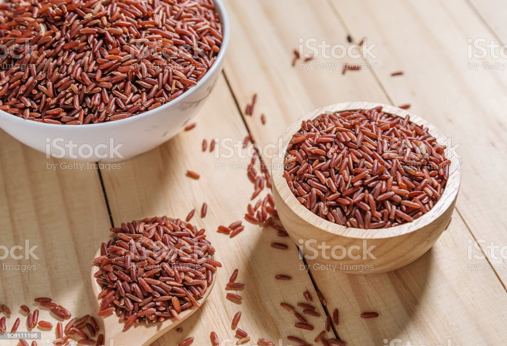 Rice berry in wooden bowl on wood background stock photo