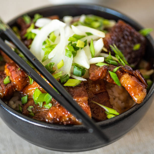 Rice bowl and fried pork belly, close-up - a traditional asian dish: chinese, japanese and korean. stock photo