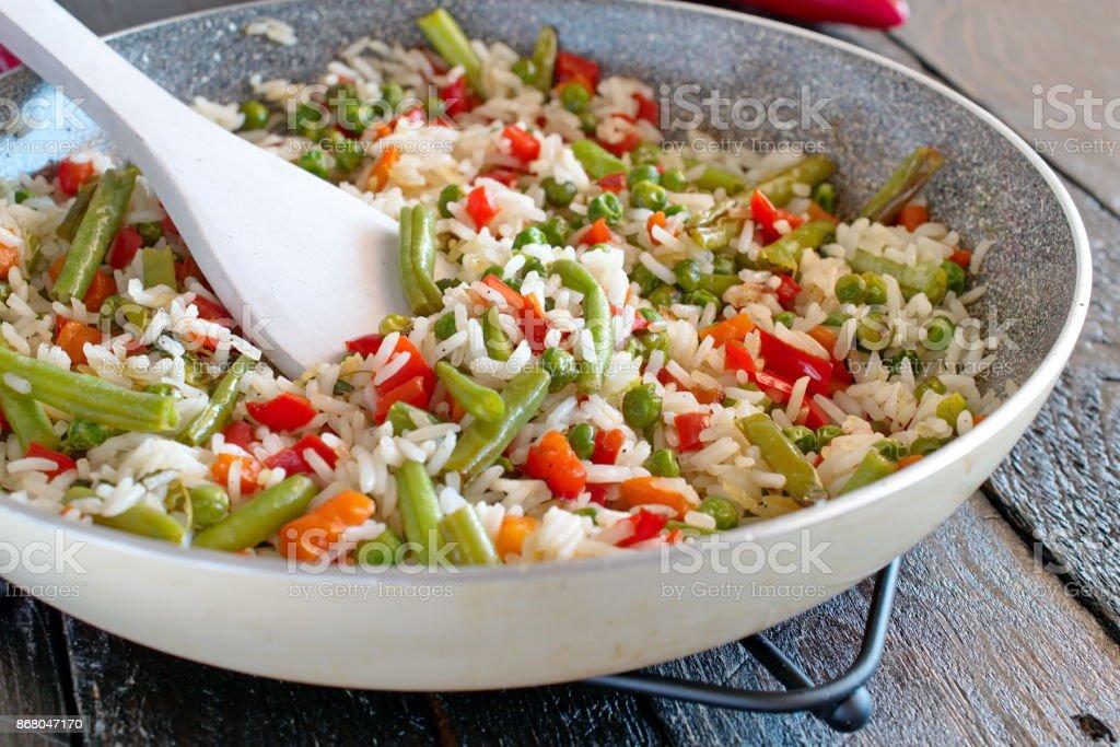 Arroz cozido com legumes e azeite em uma frigideira. - foto de acervo