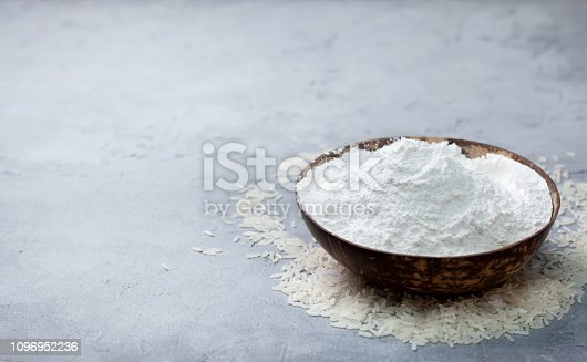 rice flour in a wooden bowl, rice on a gray concrete background. copy space