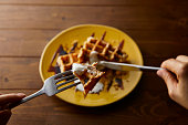 Hand eating rice flour waffle with black honey and yoghurt served on a yellow round plate.