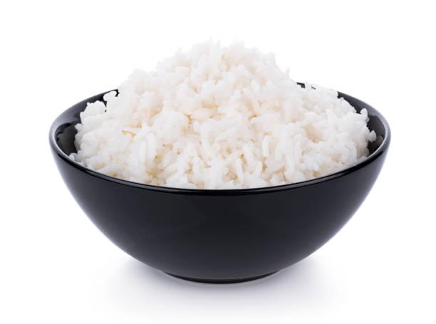 el arroz en un tazón sobre un fondo blanco - arroz comida básica fotografías e imágenes de stock