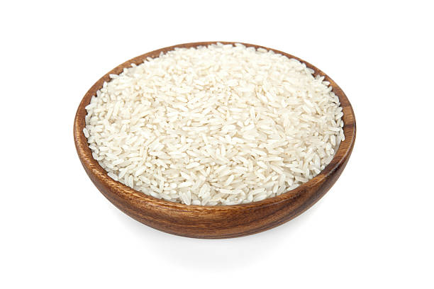 Rice in a wooden bowl Rice in a wooden bowl on white background basmati rice stock pictures, royalty-free photos & images
