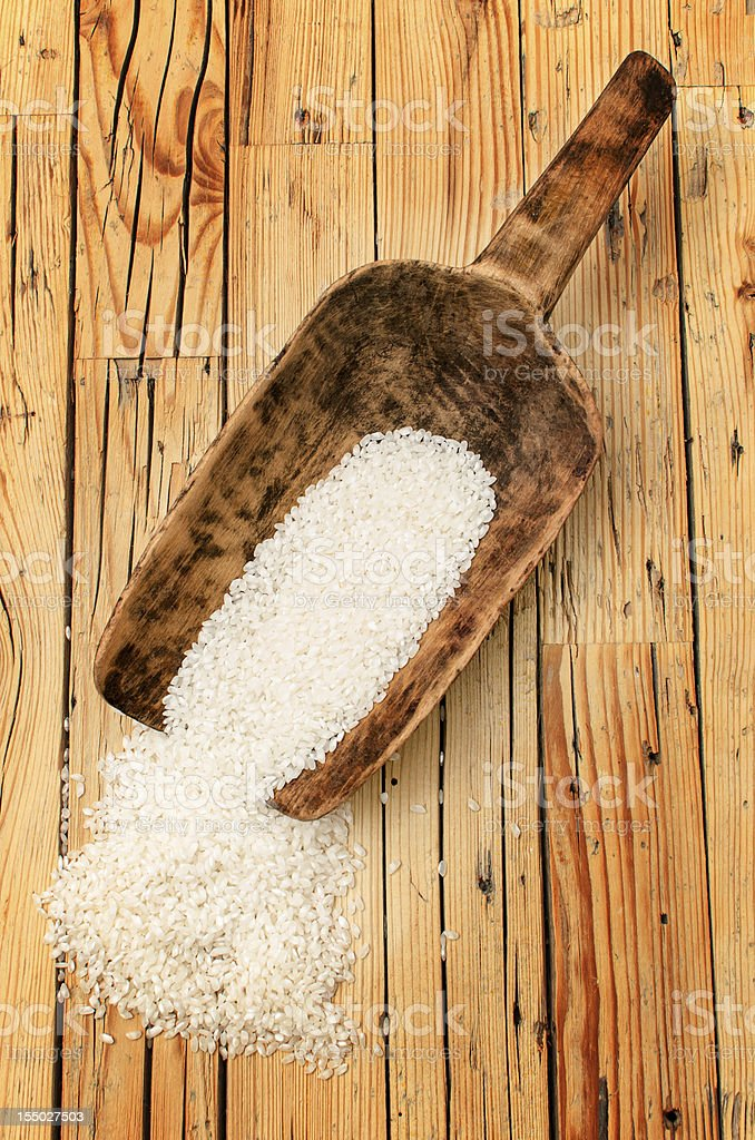 Rice in an old wooden scoop on table royalty-free stock photo