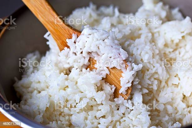 Rice In Pot Being Stirred With Wooden Spoon Stock Photo - Download Image Now