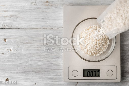 Rice in the glass bowl on the scale on the white table top view