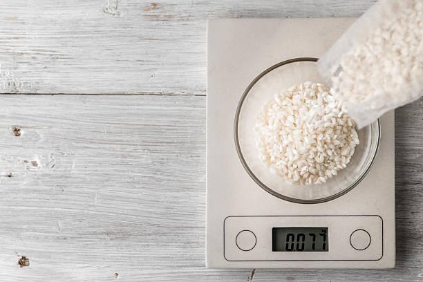 rice in the glass bowl on the scale top view - arroz comida básica fotografías e imágenes de stock