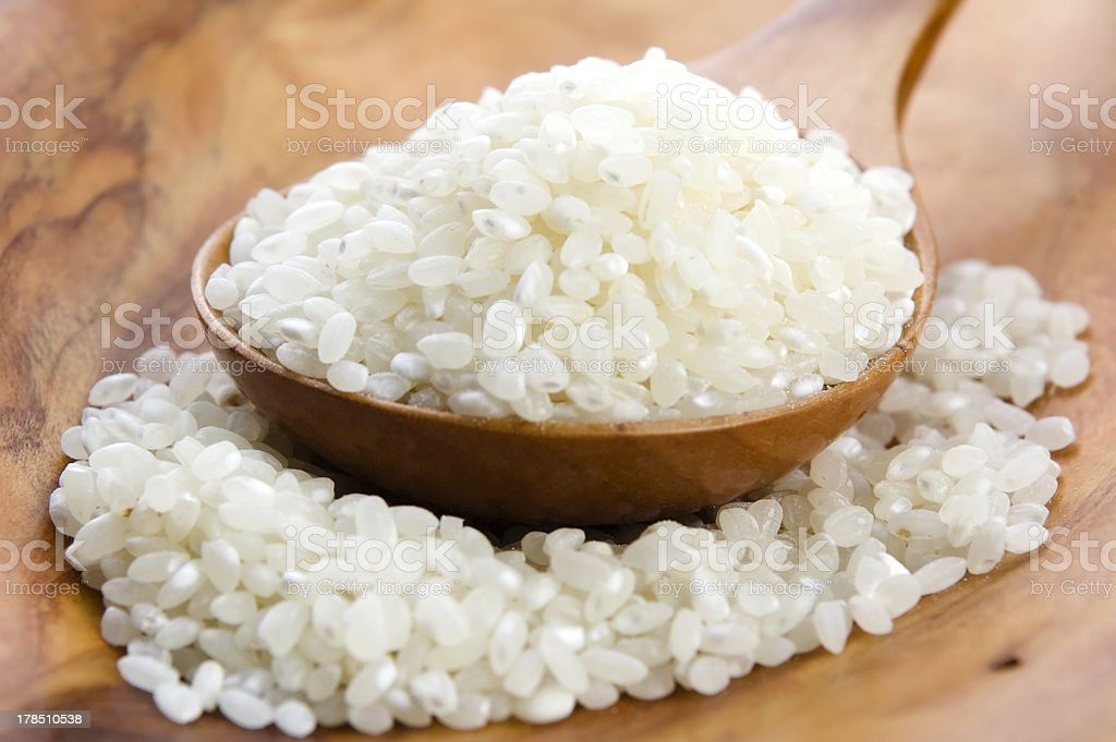 Rice in wooden spoon on kitchen table royalty-free stock photo