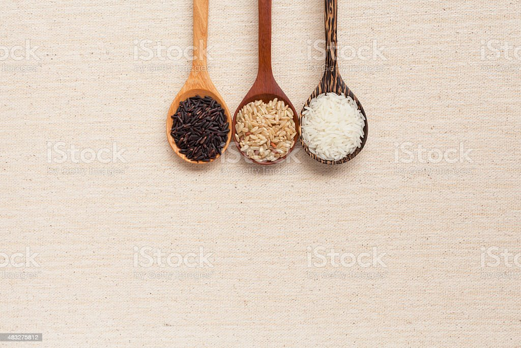 Rice in wooden spoon with space on background stock photo