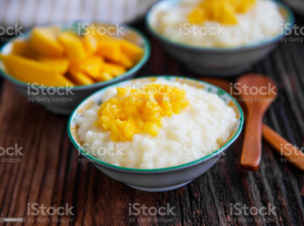 Pudim de leite de arroz com geleia de manga em tigelas com as colheres de pau, sobremesa caseira - foto de acervo