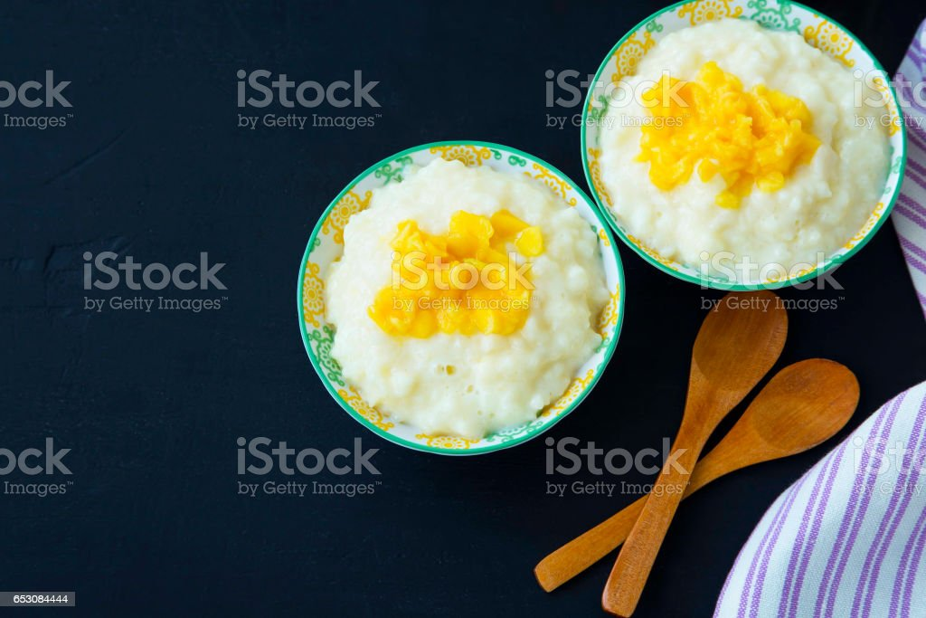 Rice milk pudding with mango jam in bowls with wooden spoons, homemade dessert stock photo