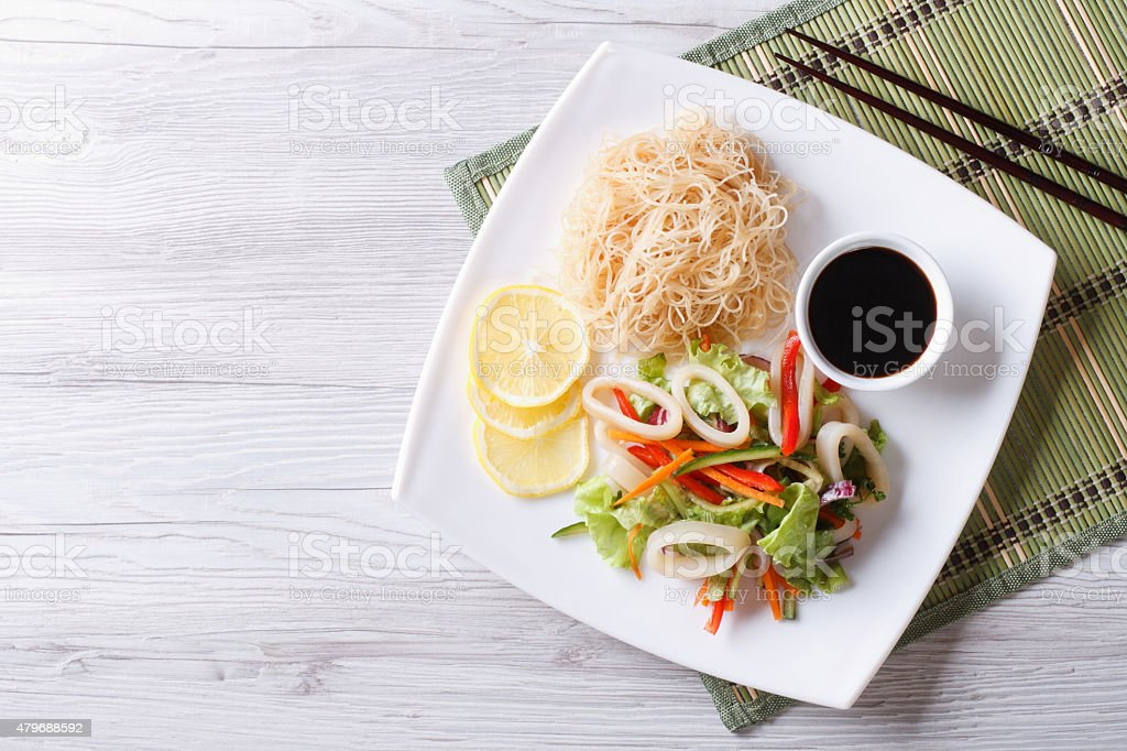 Rice noodles and vegetable salad with squid horizontal top view stock photo