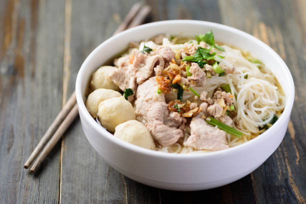 Rice noodles soup with pork and meat ball Rice noodles soup with pork and meat ball in a bowl with chopsticks on wooden table, Thai style rice noodles stock pictures, royalty-free photos & images