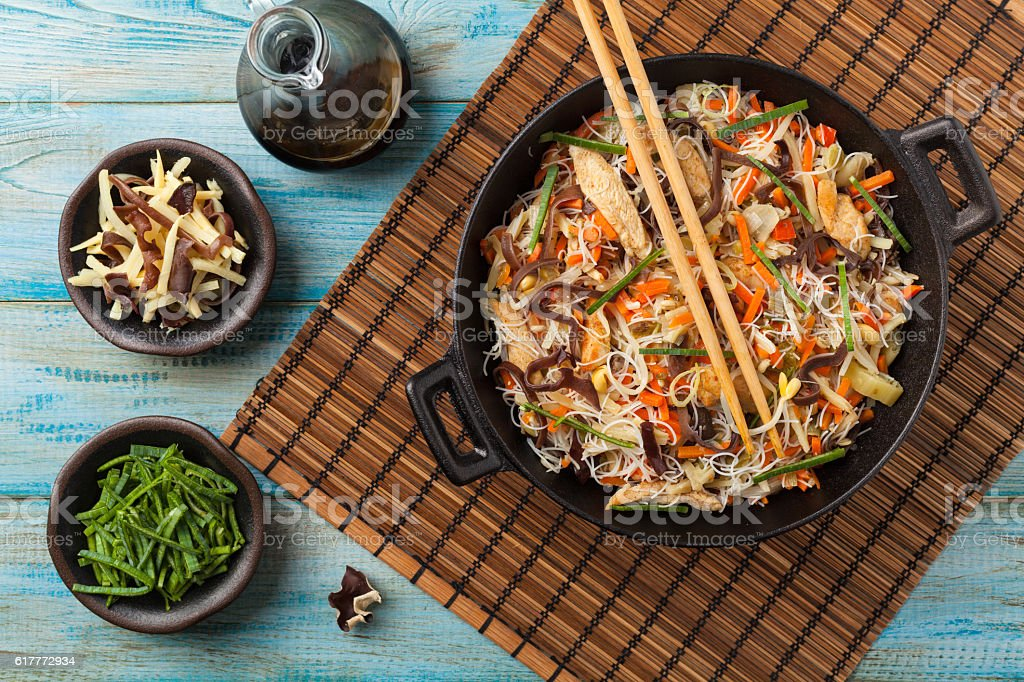 Rice noodles with chicken, mushrooms mun and vegetables in wook. stock photo