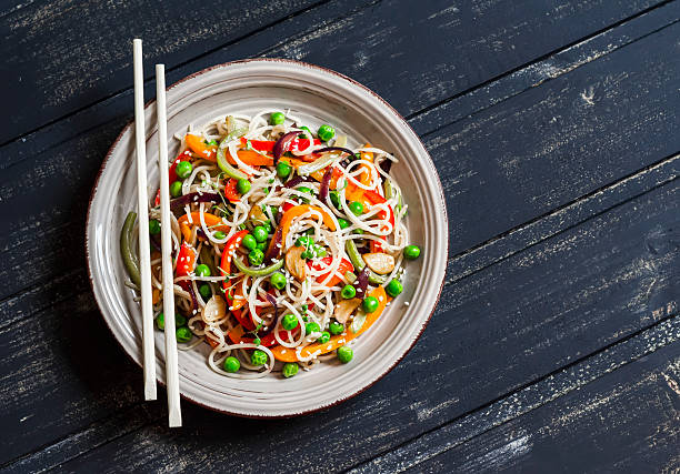 Rice noodles with vegetable stir fry on  wooden background Rice noodles with vegetable stir fry on the ceramic plate on dark wooden background rice noodles stock pictures, royalty-free photos & images