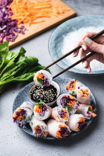 Rice paper rolls or spring rolls, asian cuisine Rice paper rolls or spring rolls with teriyaki based dipping sauce, asian cuisine. Eating spring rolls vietnamese culture stock pictures, royalty-free photos & images