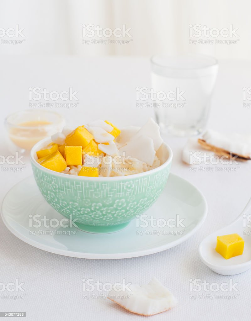 Rice pudding with mango and coconut water in a bowl stock photo