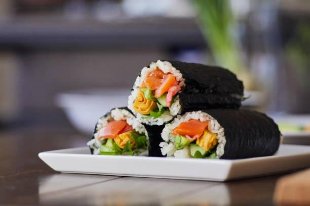risrulle insvept i en tallrik. - sushi bildbanksfoton och bilder