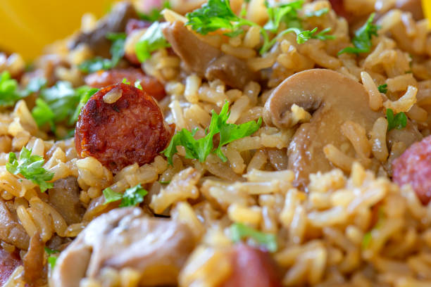 Rice salad with pork sausages, brown mushrooms and parsley stock photo