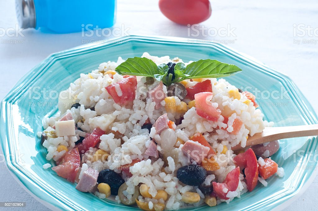 Rice salad with tomatoes, sausage and onions stock photo