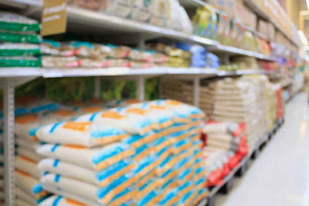 arroz estantes en supermercado almacenar borrosa fondo - arroz comida básica fotografías e imágenes de stock