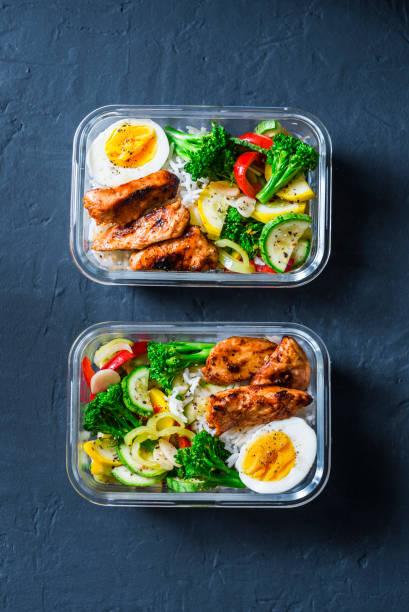 reis, geschmortem gemüse, ei, teriyaki huhn - gesunde ausgewogene lunch-box auf einem dunklen hintergrund, ansicht von oben. essen für bürokonzept - gefüllte eier stock-fotos und bilder