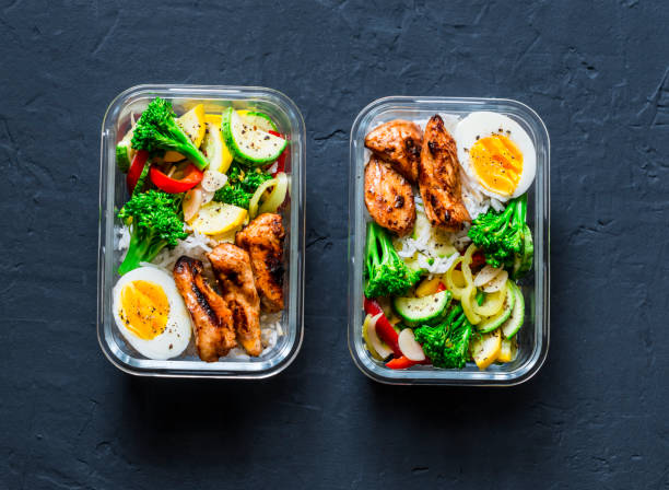 Rice, stewed vegetables, egg, teriyaki chicken - healthy balanced lunch box on a dark background, top view. Home food for office concept stock photo