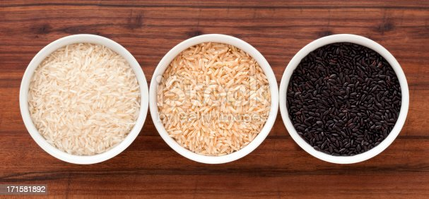 Top view of three bowls containing rice varieties (basmati, brown and black)