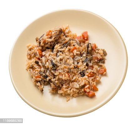 rice with braised zucchini with tomatoes and peppers on a light brown  plate. rice with vegetables isolated on white background. healthy vegetarian food. Asian cuisine top side view