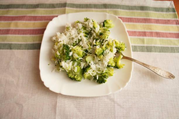 Arroz con brócoli en plato redondo blanco en el mantel blanco y verde - foto de stock
