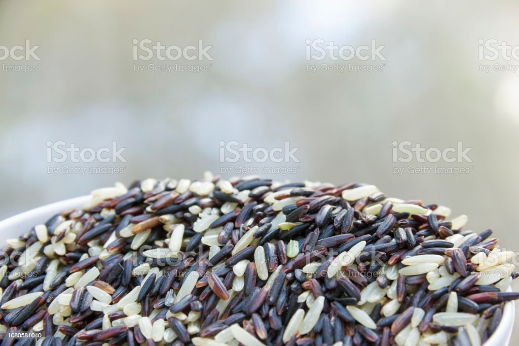 rice-berry mixed with jasmine rice in white bowl with blur background stock photo