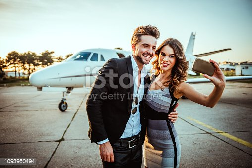 Rich, successful couple embracing each other and taking a selfie in front of a private jet parked on an airport taxiway.