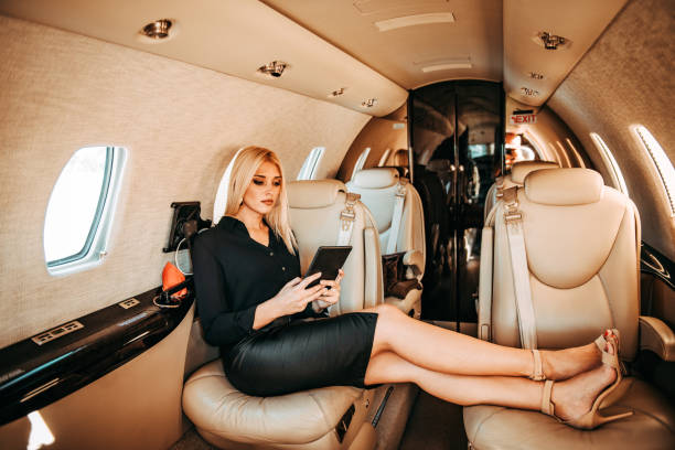 Rich blond female CEO using a digital tablet while sitting comfortably with feet up on a private jet stock photo