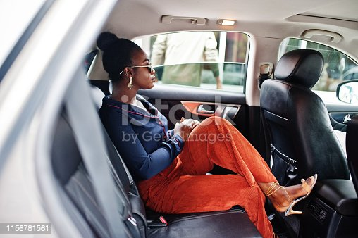 Rich business african woman on sunglasses sit at suv car with black leather seats.