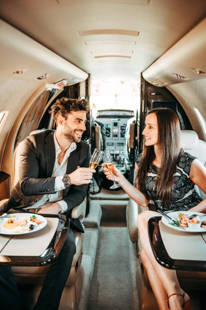 Rich business couple having a canapé appetizer and making a toast while flying in a private jet Successful business couple eating a canapé meal while flying in a private airplane. They are making a toast with champagne flutes. status symbol stock pictures, royalty-free photos & images
