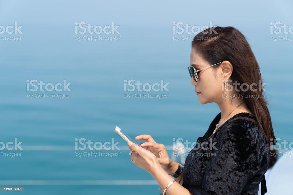 Rich business woman playing smart phone on luxury yacth. zbiór zdjęć royalty-free