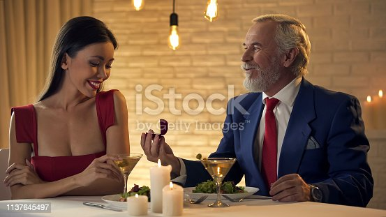 Rich businessman holding ring in gift box, anniversary present for young wife