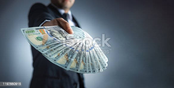 istock Rich businessman is holding a wad of money 1192880915