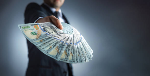 Rich businessman is holding a wad of money Rich businessman is holding a wad of money bringing home the bacon stock pictures, royalty-free photos & images