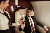 Rich businessman travelling in his private jet, meeting stewardess who brings him glass of champagner, enjoying business trip on board