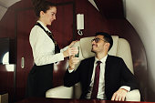Rich businessman travelling in his private jet, meeting stewardess who brings him glass of water, enjoying business trip on board