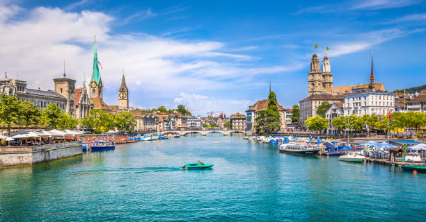 Zürich city center with river Limmat in summer, Switzerland Panoramic view of historic Zurich city center with famous Fraumunster and Grossmunster Churches and river Limmat at Lake Zurich on a sunny day with clouds in summer, Canton of Zurich, Switzerland fraumunster stock pictures, royalty-free photos & images