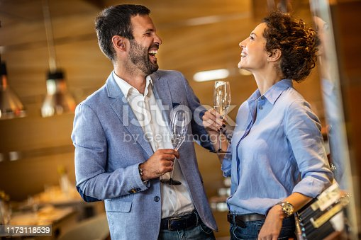 Romantic couple laughing while holding glasses of sparkling wine next to a wine rack in a restaurant.