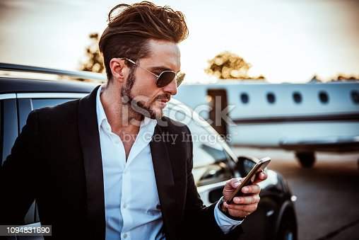 istock Rich entrepreneur using a mobile phone with a luxurious black car and a private jet parked behind him 1094831690