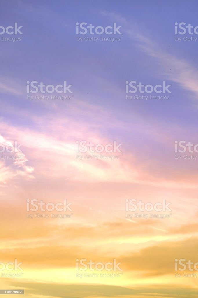 Rich golden sunset against blue sky with swirling cloud royalty-free stock photo