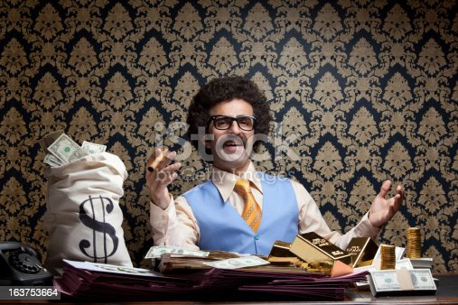 Horizontal photo of rich man posing with money bags, gold ingots and dollar bills and sitting on table.He has long hair and mustache and wearing a blue waist and a yellow necktie.Wallpaper is on the background.Model is holding cigar in right hand.Vignette light effect achieved during shot.Full frame DSLR camera was used.