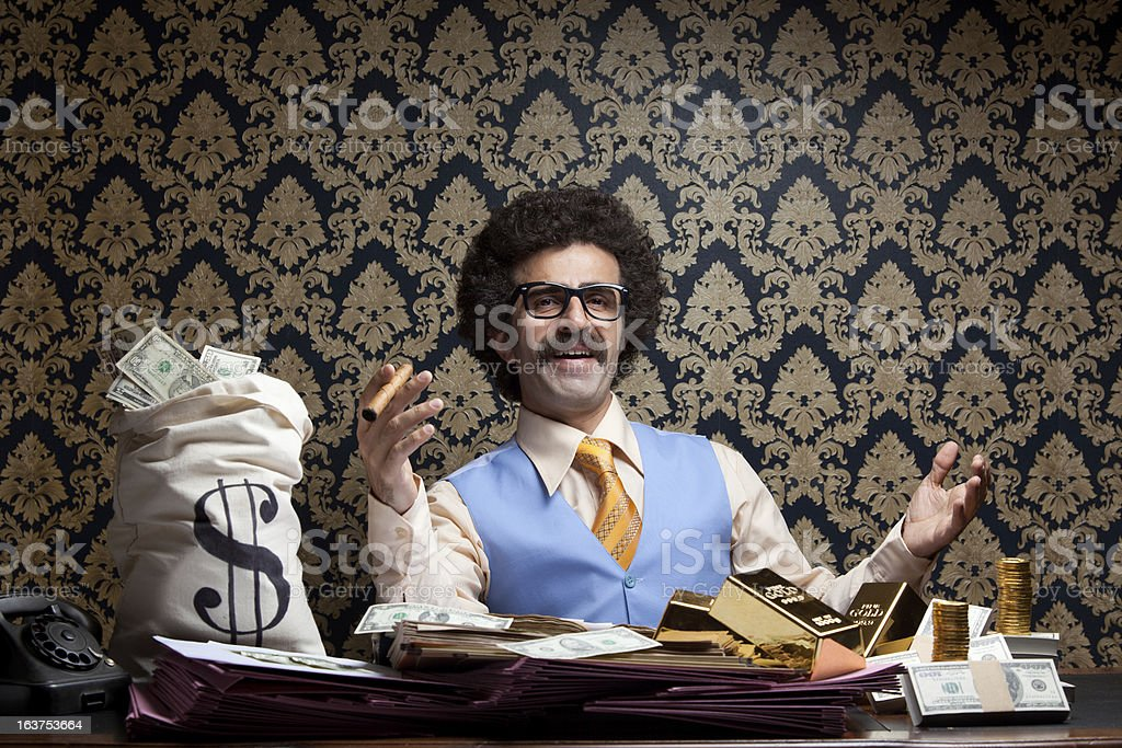 Rich man posing with money bags, gold bullions, dollar bills stock photo