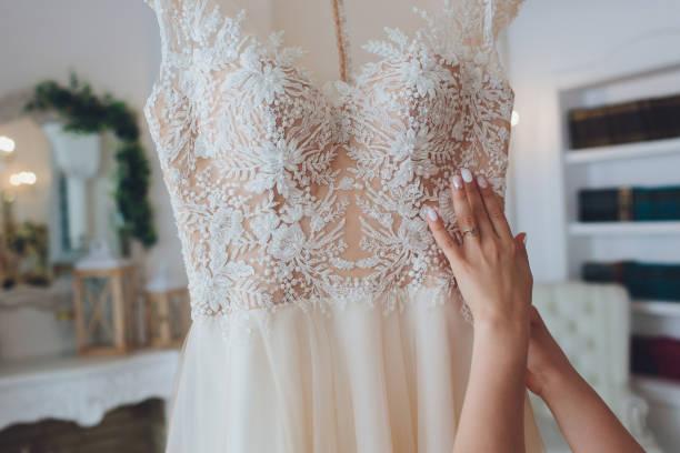 Reiche rosa Hochzeitskleid hängt an einem Kronleuchter in einem weißen Raum. – Foto