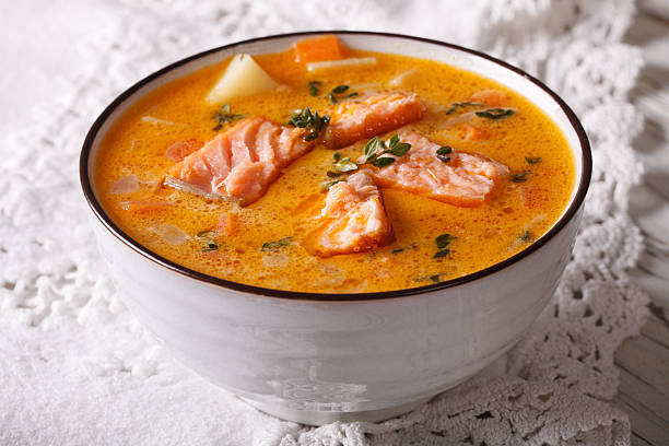 Rich soup with salmon, vegetables and thyme close-up stock photo